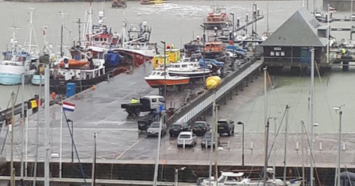 Man dies after being washed off harbour wall as wind and rain batter Britain