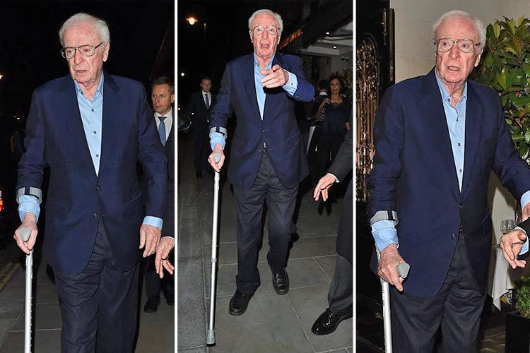 Acting legend Michael Caine uses walking stick during night out after recent ankle break