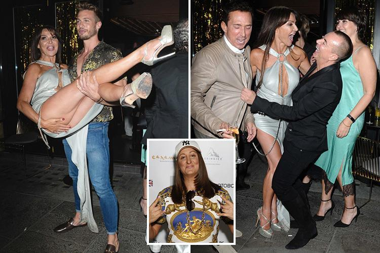 Lizzie Cundy nearly flashes her knickers as she's carried out of her celeb-studded 48th birthday bash by hunk