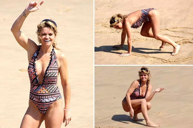 Danniella Westbrook crawls around on sand and writes a cryptic message wearing a very plunging halterneck swimsuit