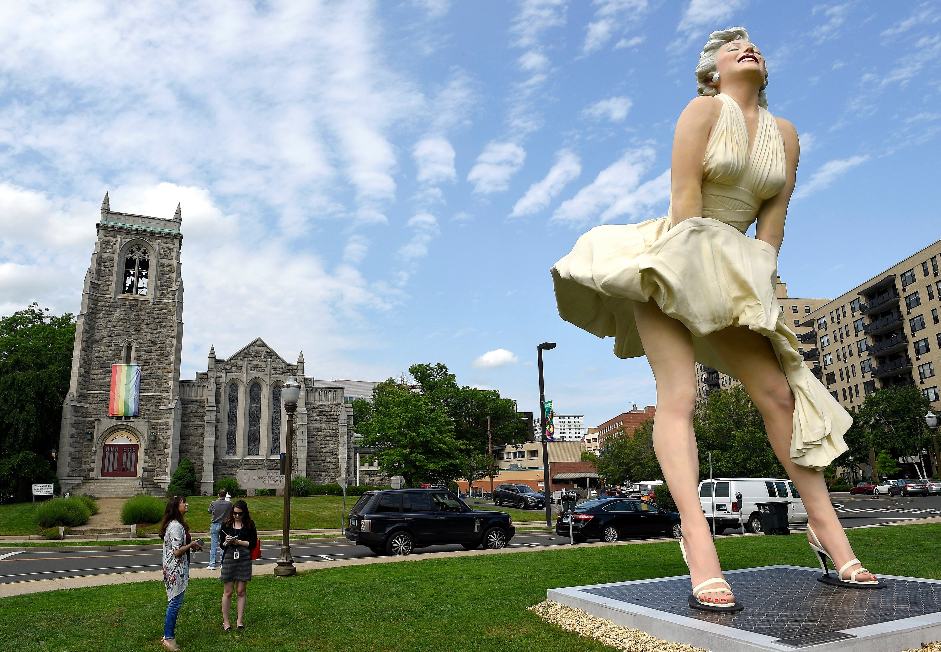 Statue of Marilyn Monroe famously exposing her rear displayed near church