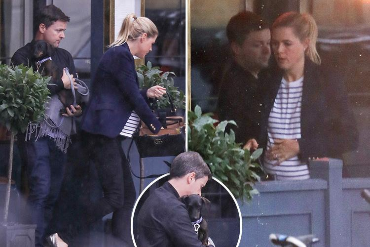 Declan Donnelly shields his beloved sausage dog from the rain during lunch out with pregnant wife Ali Astall