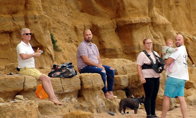 Family with baby ignore signs and sit under cliff prone to rockfalls