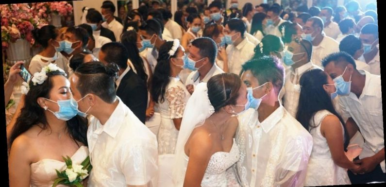 Hundreds of couples wear masks to kiss at mass wedding amid coronavirus fears