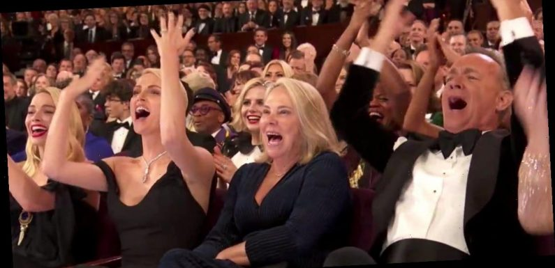 Tom Hanks and Charlize Theron led a cheer to turn the lights back on the Oscars stage after the show seemed to cut the 'Parasite' acceptance speech short
