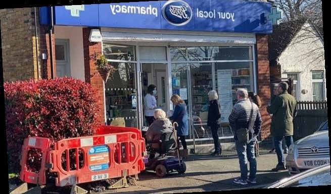 Pharmacist in mask and gloves serves customers  outside Boots store