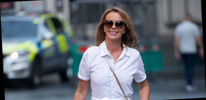 Amanda Holden flashes tanned legs in revealing white dress as she carries large picture of herself