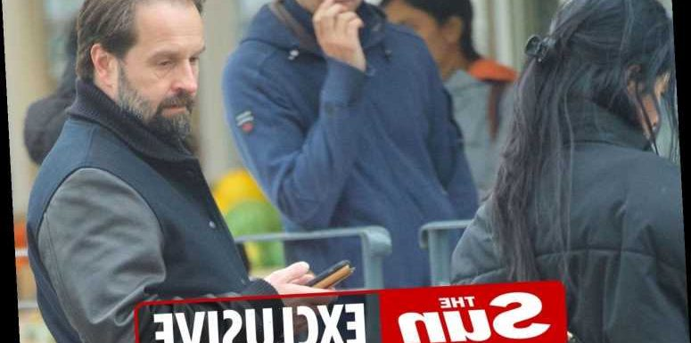 Alfie Boe steals a glance at stunning jeans-wearing brunette while out in London
